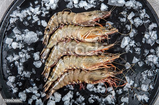 istock Raw whole fresh uncooked prawns shrimps on marble plate, stone background. Top view with copy space. 1289608862