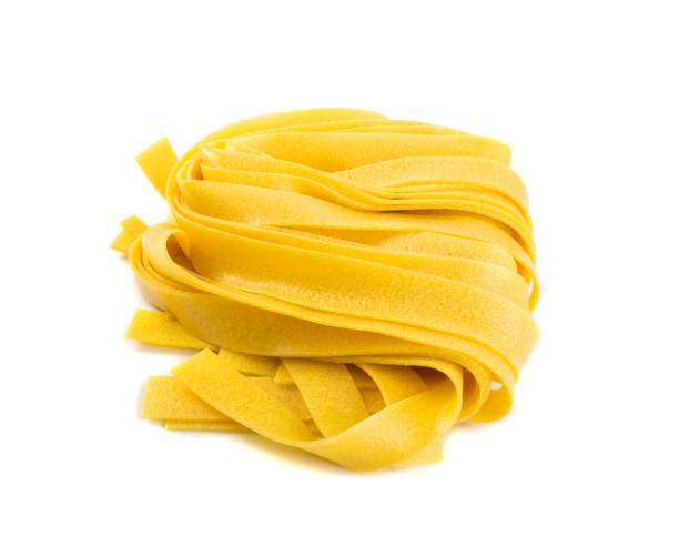 Raw yellow italian pasta pappardelle, fettuccine or tagliatelle Raw yellow italian pasta pappardelle, fettuccine or tagliatelle close up. Egg homemade dry ribbon noodles, long rolled macaroni or uncooked spaghetti isolated uncooked pasta stock pictures, royalty-free photos & images