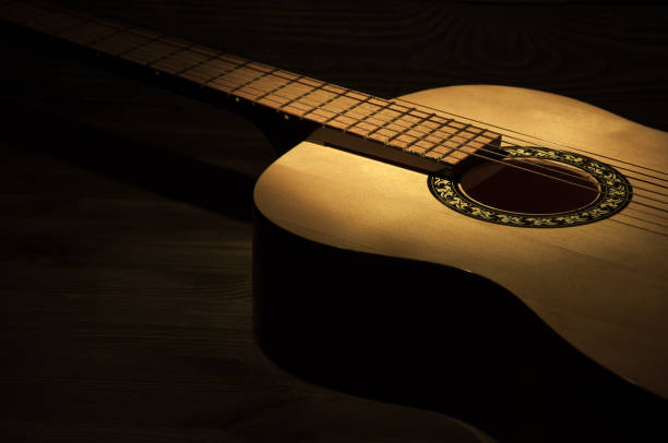 A ray of light falls on an acoustic guitar lying on a wooden textured background. stock photo