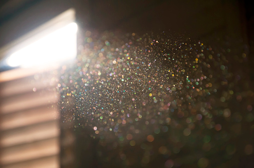 A ray of sun coming through the wooden shutters, illuminates dust on the inside of a dark room.