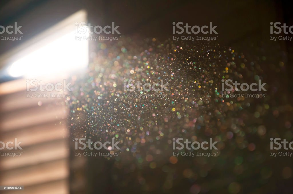 A ray of sun coming through the wooden shutters, illuminates dust on the inside of a dark room. stock photo