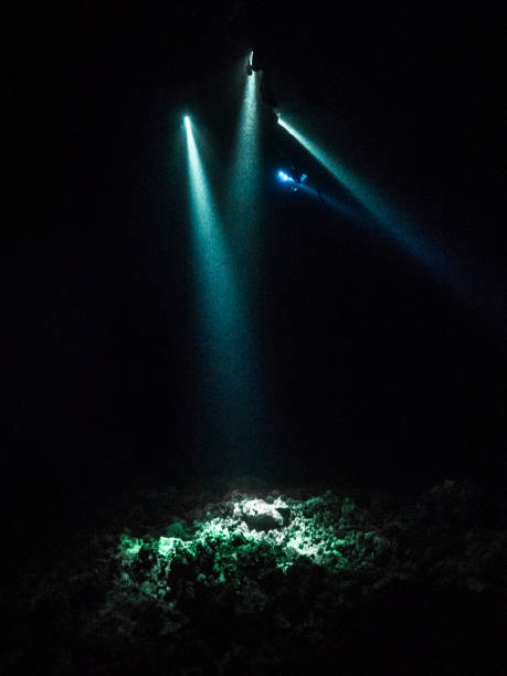 Rays of light under water at night stock photo