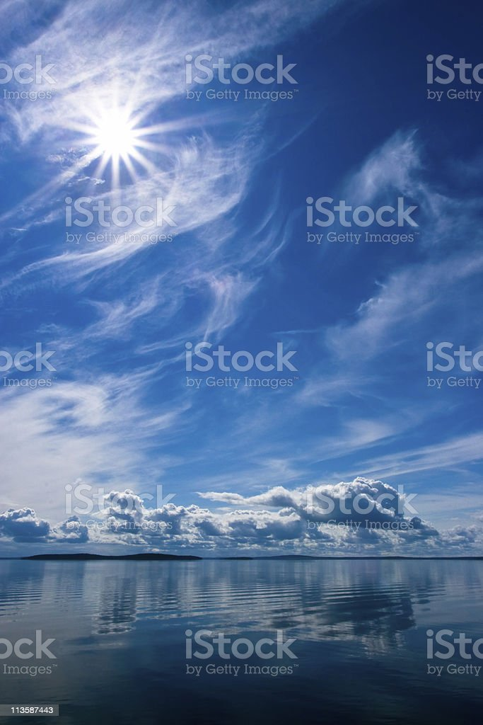 Rays of Sun on Blue Sky Reflecting in Lake royalty-free stock photo