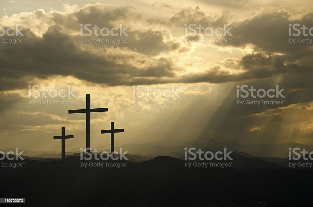 Rays of sun through the clouds on three black crosses royalty-free stock photo