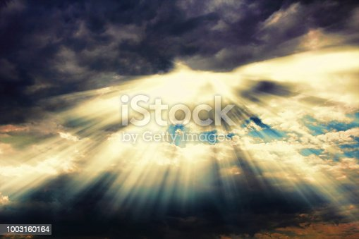 istock Rays of sunlight coming through dramatic clouds 1003160164