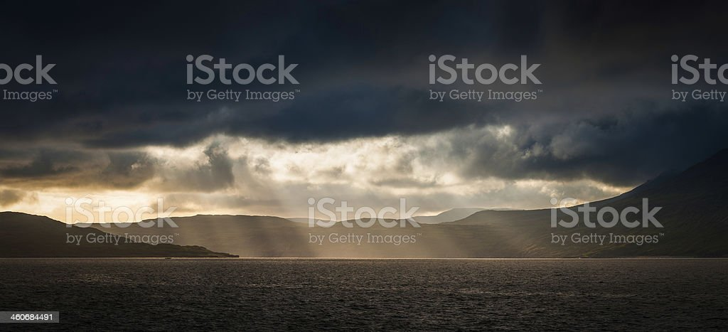 Rays of sunlight piercing storm clouds over ocean mountain panorama stock photo