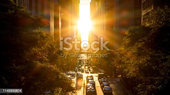 Rays of sunlight shine on the cars and buildings along 42nd Street in Midtown New York City