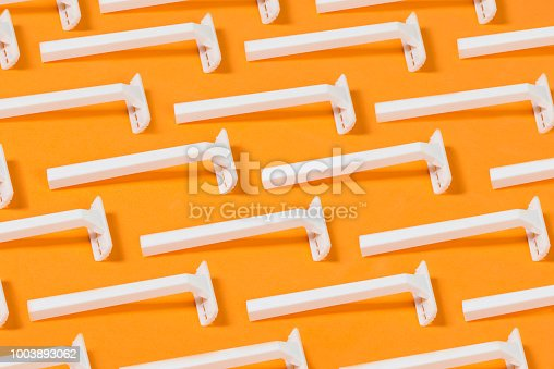 istock Razor Blades On Orange Background 1003893062