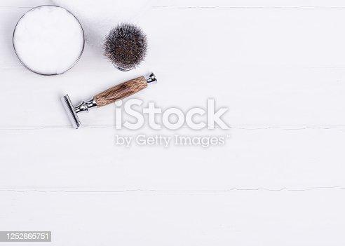 Razor, brush, and shaving foam on a white background.