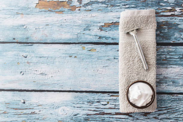 razor, shaving cream and towel on wooden background - shaving cream stock pictures, royalty-free photos & images