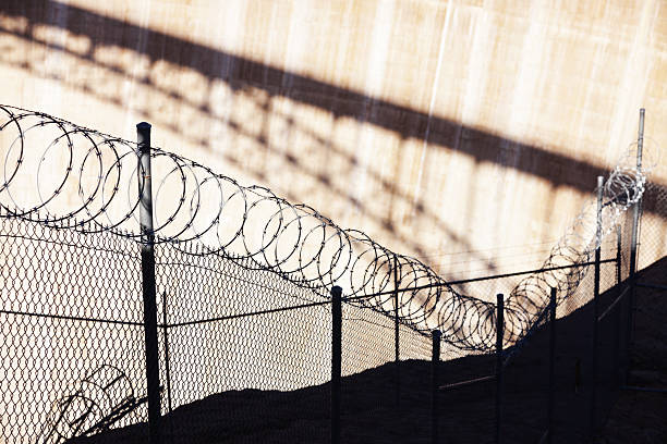 Razor Wire Barbed Fence Barrier Razor wire barbed chain link fence barrier - with bridge shadow background. deportation stock pictures, royalty-free photos & images