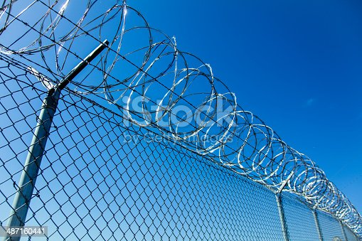Razor wire is coiled on top of a chain link fence backed by a deep blue sky.