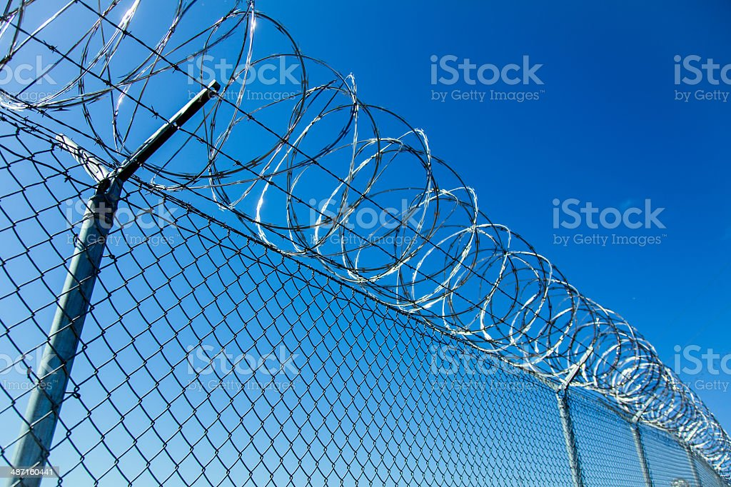 Razor Wire Coiled on Chainlink Fence with Deep Blue Sky stock photo