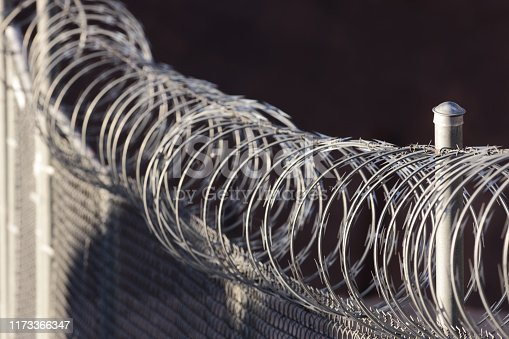 A razor wire topped fence runs diagonally from lower right to upper left of frame in a horizontal composition.  Early morning sun illuminates the razor coils while some of the image falls into shadow - mostly the backdrop.  Foreground focus on razor coils and metal fence post.