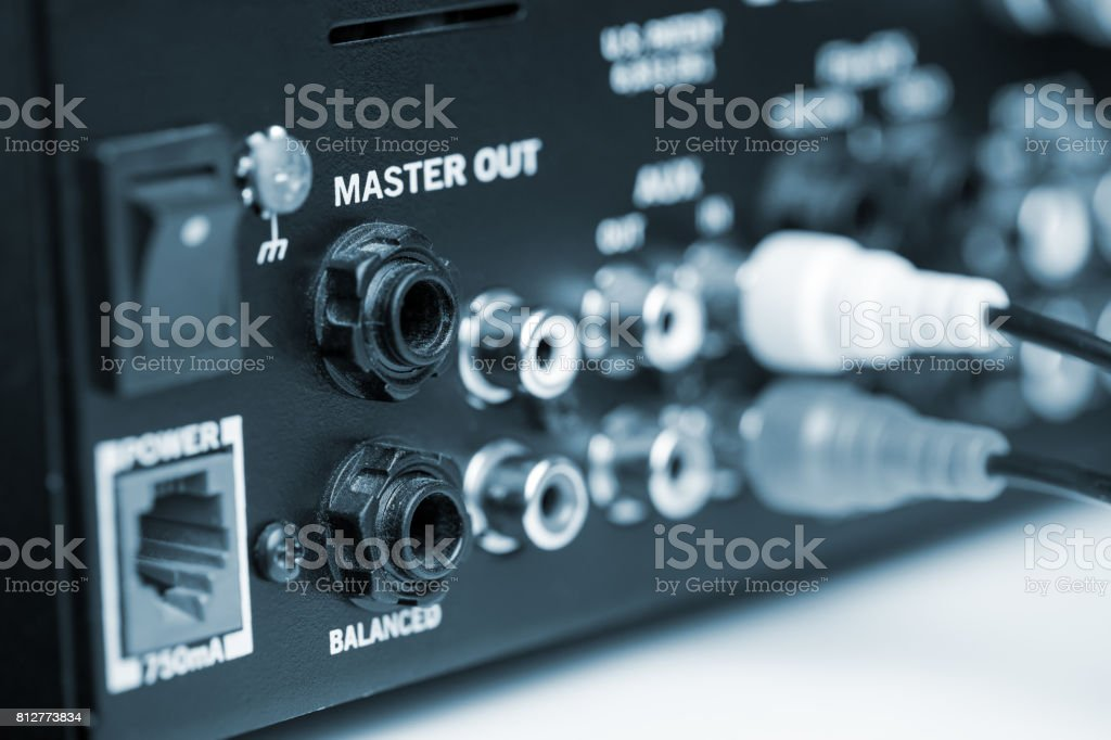 Rca cables on back panel of dj mixer. Blue tone stock photo