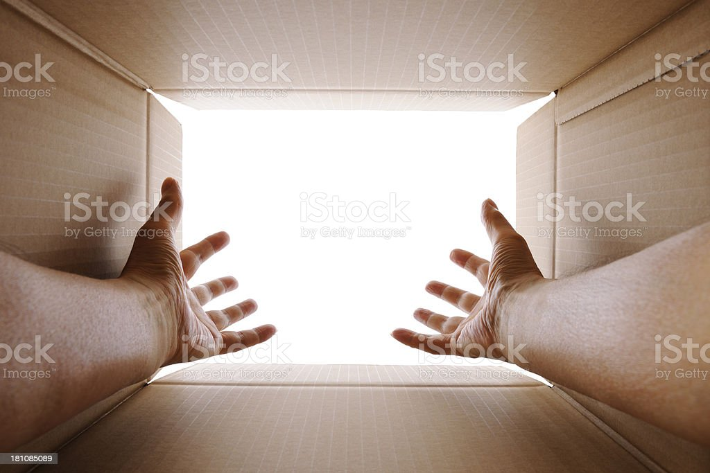 Reach out a hand from  cardboard box against white background royalty-free stock photo