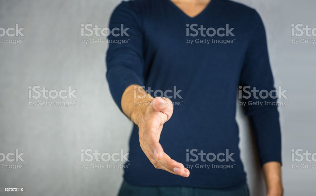 reach out hand by man, on light grey background stock photo