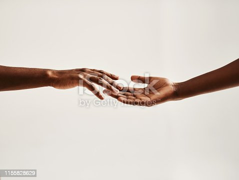 Closeup shot of two unrecognisable people reaching for each other with their hands