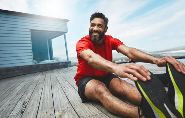 Reaching for a healthier lifestyle Shot of a man stretching before his workout touching toes stock pictures, royalty-free photos & images