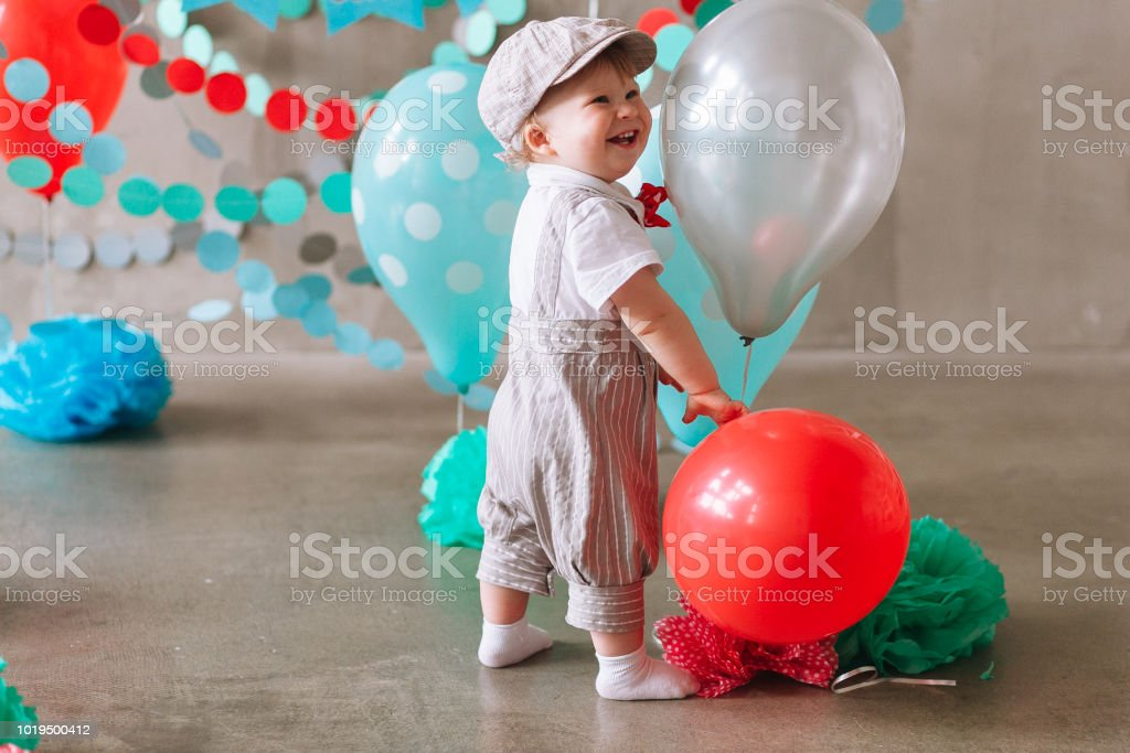 Reaching for balloons Baby boy sitting on floor reaching for balloons on his first birthday stock photo