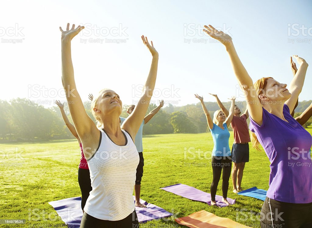 Reaching for good health - Yoga Group of people reaching toward the skies as they do their yoga class outdoors 20-29 Years Stock Photo