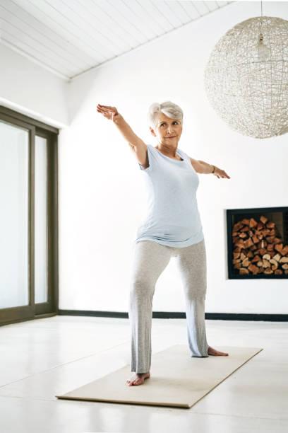atteindre pour améliorer la santé, un étirement à la fois - une seule femme senior photos et images de collection