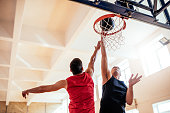 Photo of two basketball players dunking basketball in hoop.