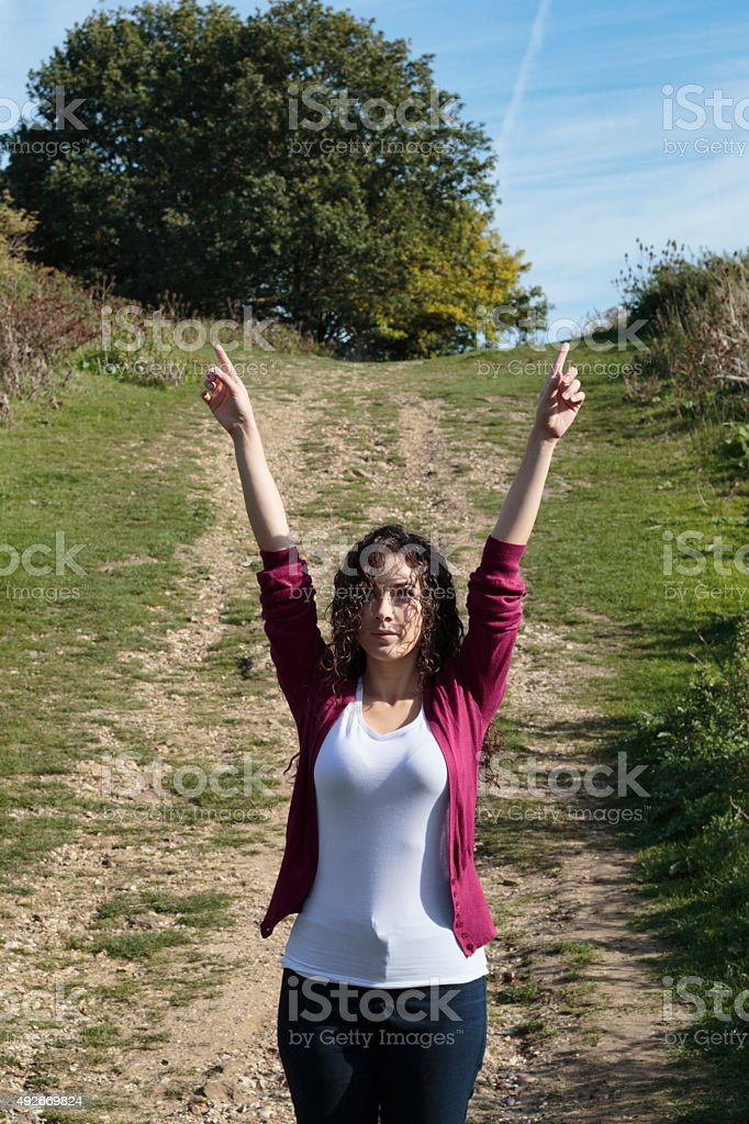 Pointing uphill to the sky Canadian outdoor girl stock photo