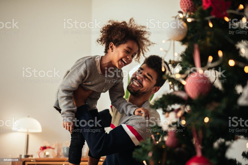Reaching for the top of the Christmas tree! stock photo