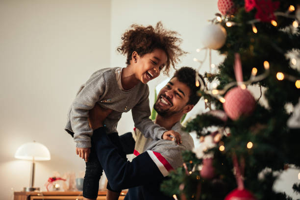 reaching for the top of the christmas tree! - christmas stock photos and pictures
