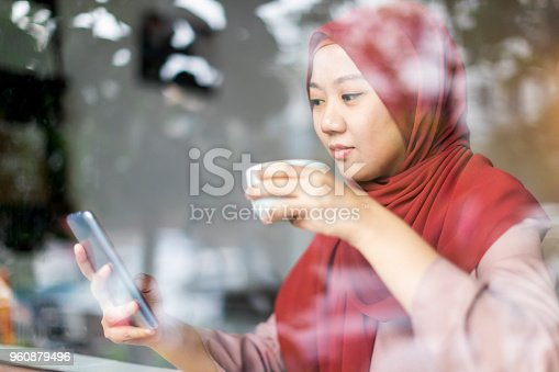 Young woman in a hijab looking over her messages at a cafe while sipping some tea.