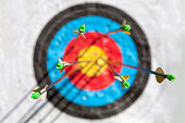 One out of six arrows in the bull's-eye of an archery target. Selective focus with the focus being on the back end of the arrow, with an out of focus target.
