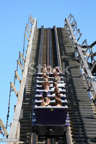 Thrill-seeking teens on a vintage wooden roller coaster in Vancouver, Canada.