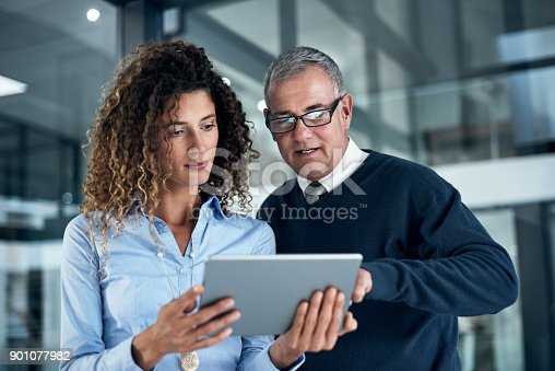 Shot of two businesspeople working late on a digital tablet in an office