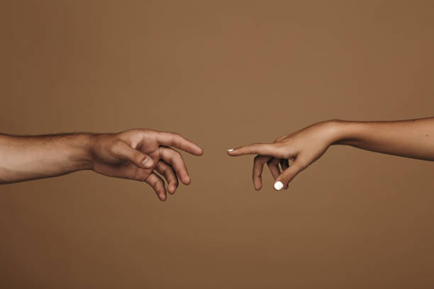 Reaching to one another Close up of man and woman hand about to touch with index finger. Couple in love reaching to one another in front of brown background. approaching stock pictures, royalty-free photos & images