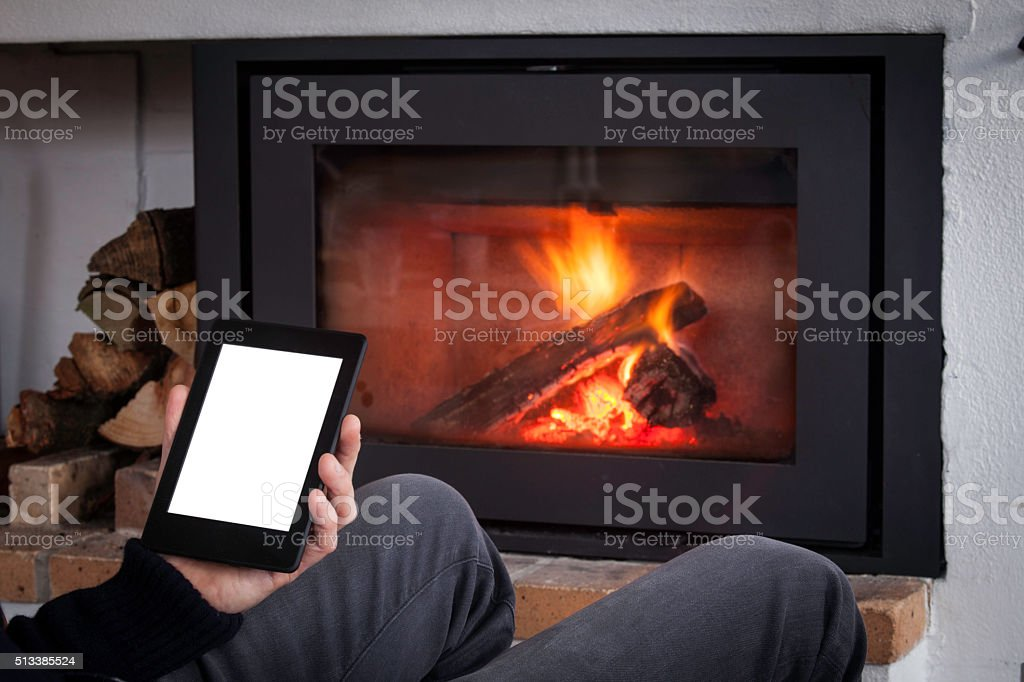 Read a ebook by the fireplace stock photo