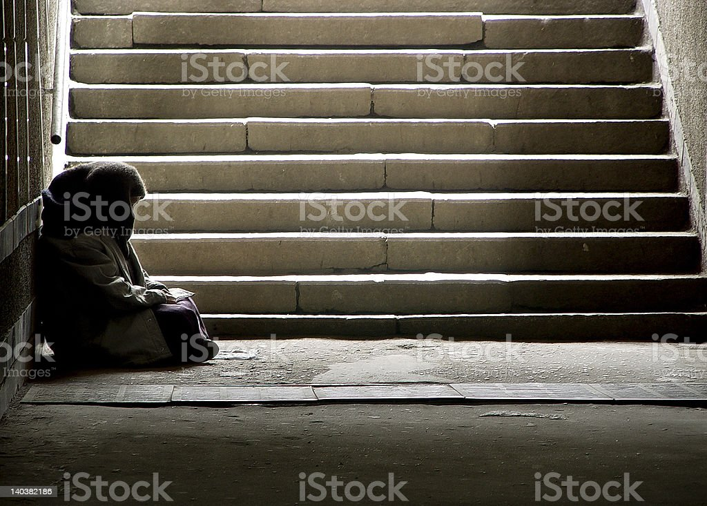 Read photo of beggar woman reading the book in undergrund subway Active Seniors Stock Photo