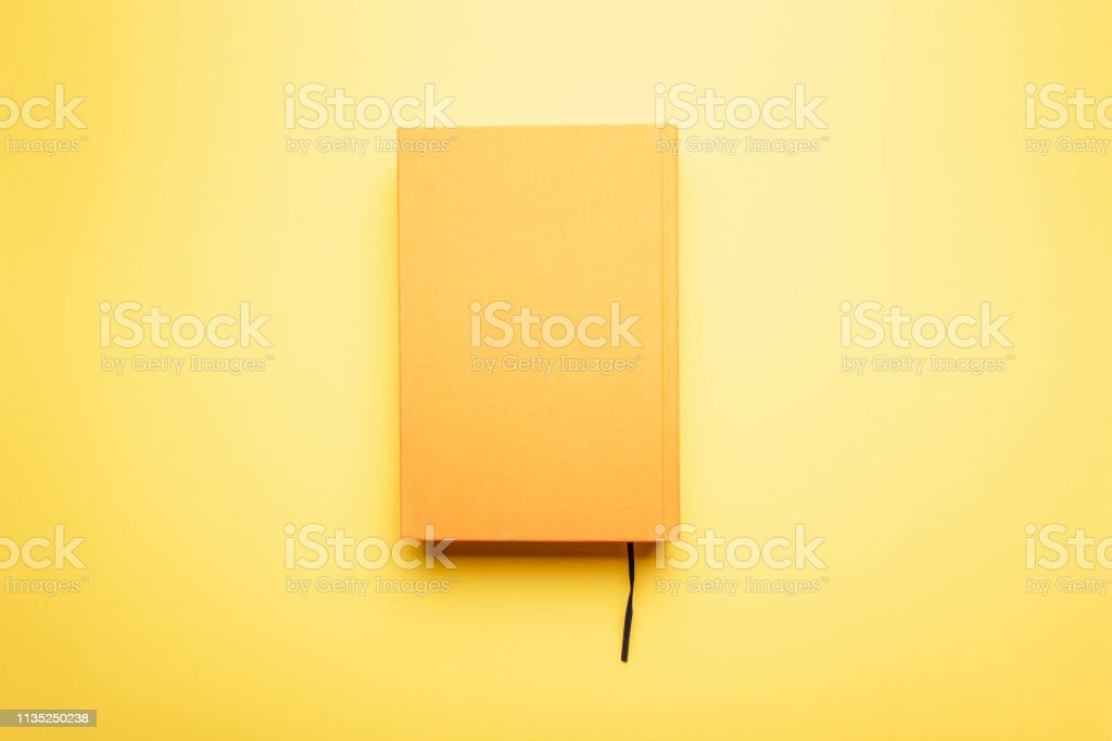 Read to the end of the literary work with a bookmark lies on a bright table. The book and the background is yellow.