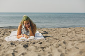 Low angle view of young woman lying down on the sand, reading a book and enjoying her summer vacations at the beach.