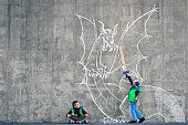 Boy reading a book and imagining himself fighting a dragon. Importance of reading and existence of non-visual media. Dragon chalk drawing on the concrete wall. Natural light.