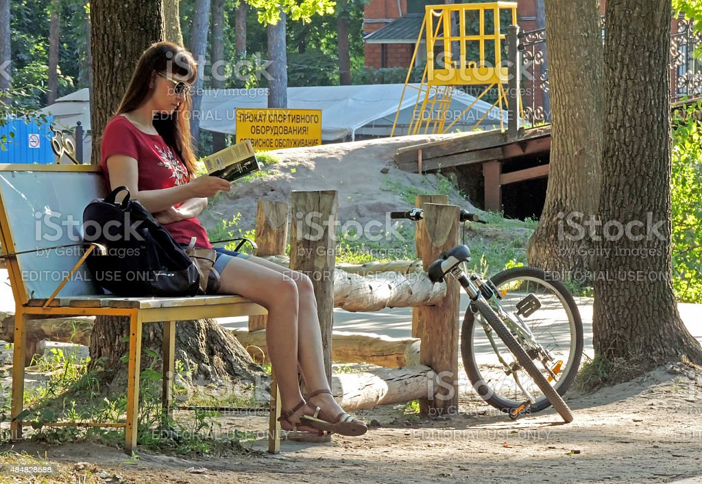 Reading a book in the park stock photo