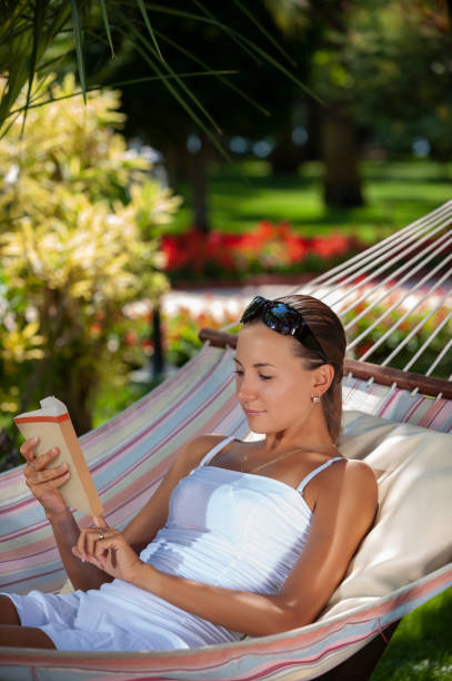 Reading a book on hammock in a peaceful garden during holiday stock photo
