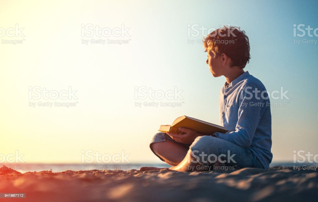 Reading a book on the beach at sunset stock photo