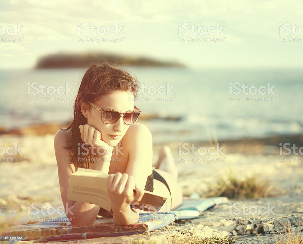 Reading a book on the sunny beach stock photo