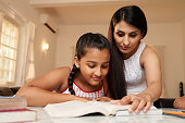 Girl reading a book with her teacher at home