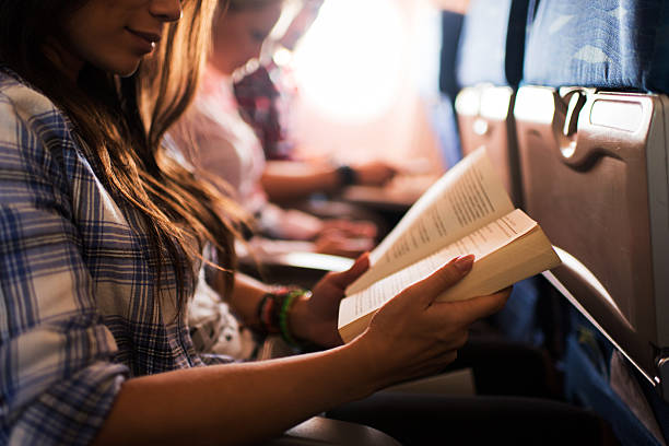 Reading a book while travelling by airplane. stock photo
