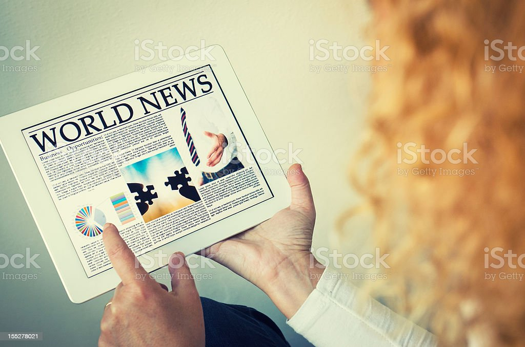Reading a digital Newspaper on contemporary Tablet royalty-free stock photo