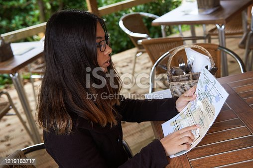 A pretty young woman reading a menu in an outdoor cafe.
