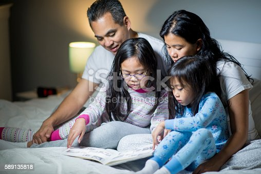 A family of four are reading books together in bed before their daughters need to go to sleep.