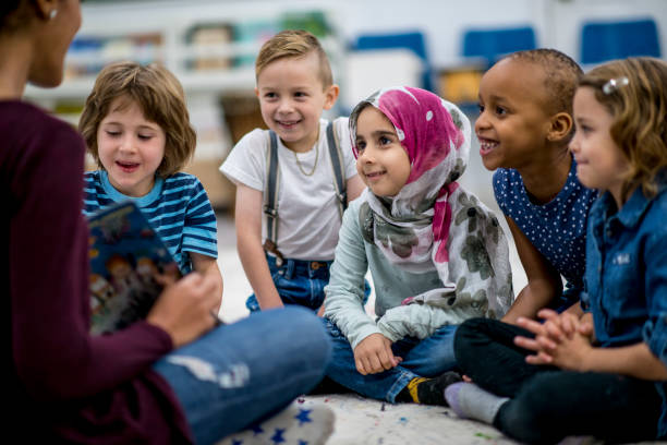 Reading A Storybook A multi-ethnic group of school children are indoors in a classroom. They are wearing casual clothing. They are sitting on the floor and eagerly listening to their teacher read a storybook. elementary school stock pictures, royalty-free photos & images